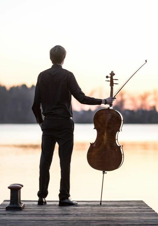 A musician standing in front of a beautiful lake